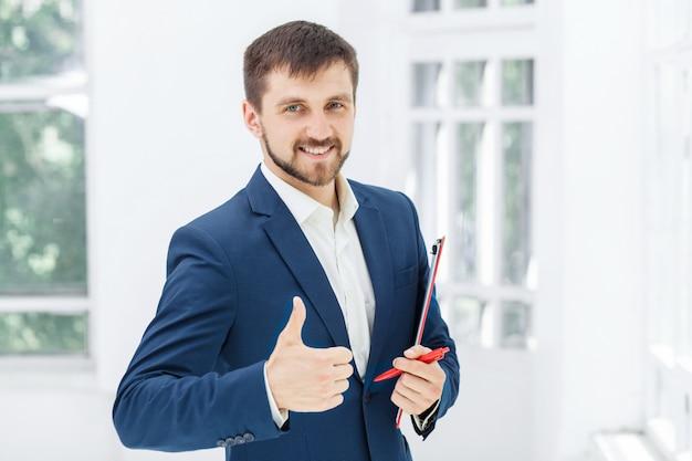 De glimlachende mannelijke beambte tegen wit bureau