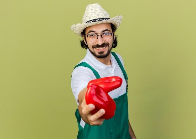 De glimlachende mannelijke tuinman in optische glazen die tuinierende hoed dragen houdt rode paprika's