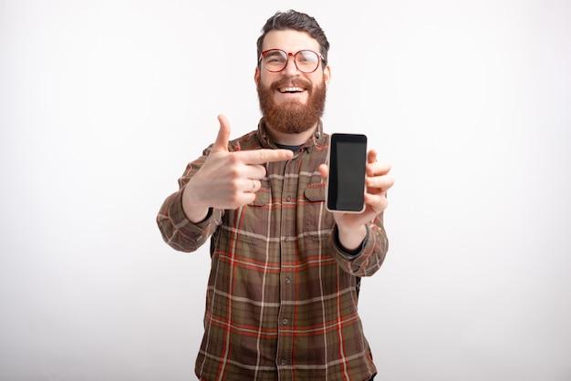 De glimlachende mens die glazen en baard dragen richt op zijn telefoon.