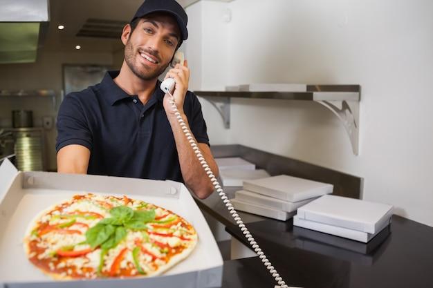 De glimlachende mens die van de pizzalevering een orde over de telefoon nemen die een pizza tonen