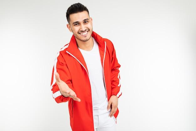 De glimlachende mens in een sporten rood kostuum houdt een helpende hand op een witte achtergrond met exemplaarruimte stand