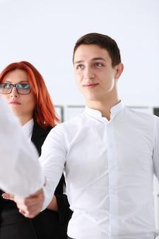De glimlachende mens in kostuum schudt handen als hallo in bureau