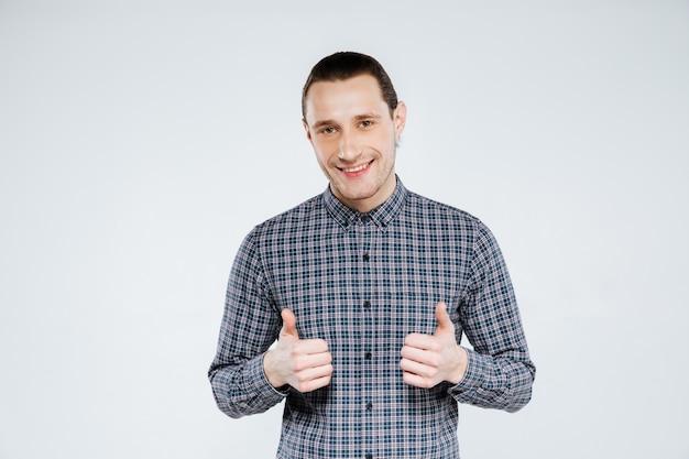 De glimlachende mens in overhemd het tonen beduimelt omhoog