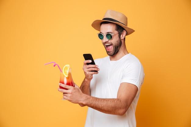 De glimlachende mens met cocktail maakt telefonisch foto