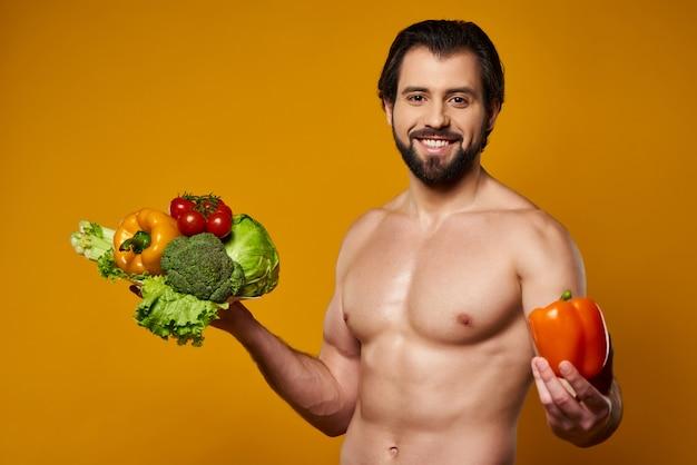 De glimlachende mens met groenten blijft dichtbij gele muur