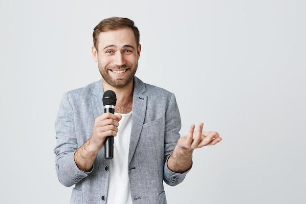De glimlachende mens met microfoon voert stand-up uit