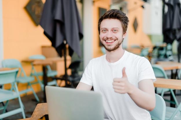 De glimlachende mens toont duimen terwijl het werken aan laptop