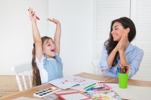 De glimlachende moeder en de dochter die voor lessen voorbereidingen treffen en trekken bij de lijst met potloden en verven