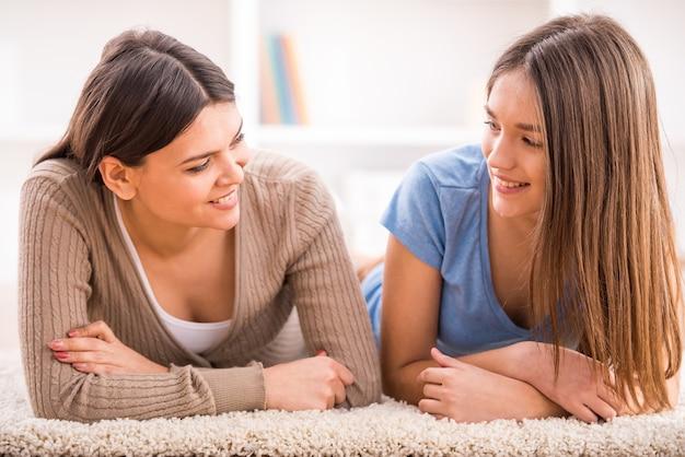 De glimlachende moeder en haar tienerdochter liggen op de vloer.