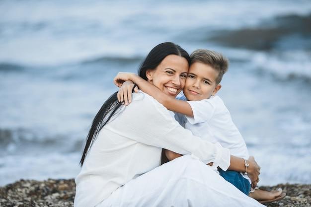 De glimlachende moeder en zoon omhelzen en kijken strak, zittend op het rotsachtige strand dichtbij de stormachtige zee