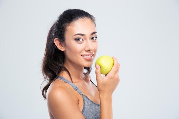 De glimlachende mooie appel van de vrouwenholding die op een witte muur wordt geïsoleerd. kijkend naar de voorkant