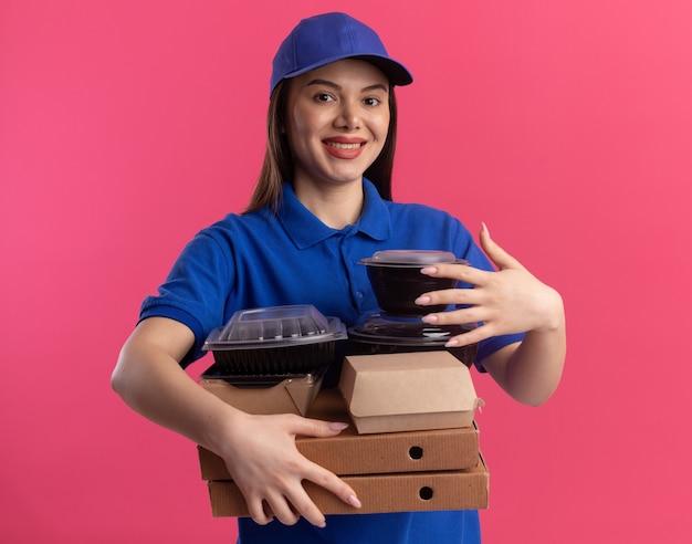 De glimlachende mooie bezorgvrouw in uniform houdt voedselpakket en containers op pizzadozen die op roze muur met exemplaarruimte worden geïsoleerd