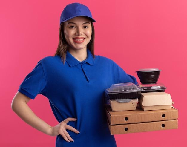 De glimlachende mooie bezorgvrouw in uniform legt de hand op de taille en houdt voedselpakket en containers op pizzadozen geïsoleerd op roze muur met kopie ruimte