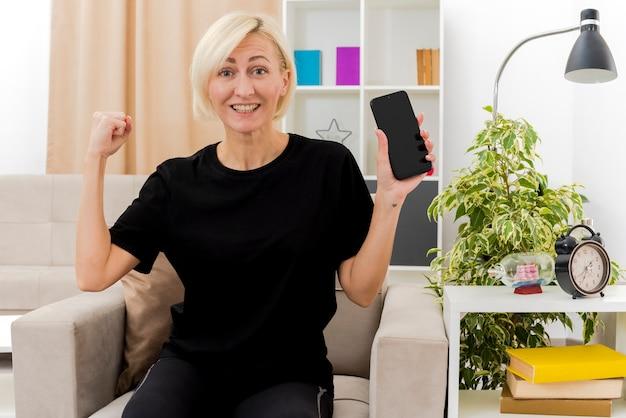 De glimlachende mooie blonde russische vrouw zit op leunstoel die vuist houdt en telefoon op zoek houdt