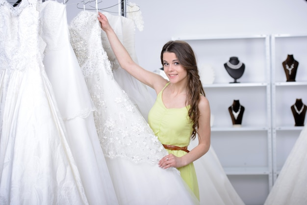 De glimlachende mooie bruid kiest witte toga bij winkel.