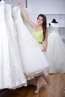 De glimlachende mooie bruid kiest witte toga in huwelijkswinkel.