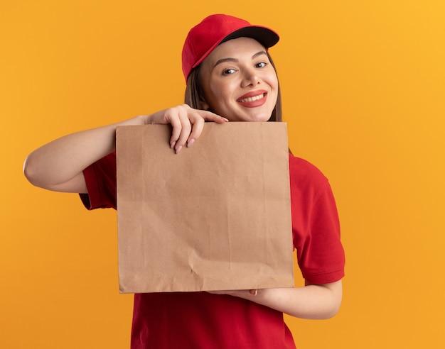 De glimlachende mooie leveringsvrouw in uniform houdt document pakket dat op oranje muur met exemplaarruimte wordt geïsoleerd
