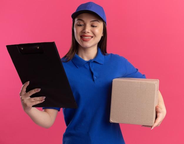 De glimlachende mooie leveringsvrouw in uniform houdt kartondoos en bekijkt klembord dat op roze muur met exemplaarruimte wordt geïsoleerd