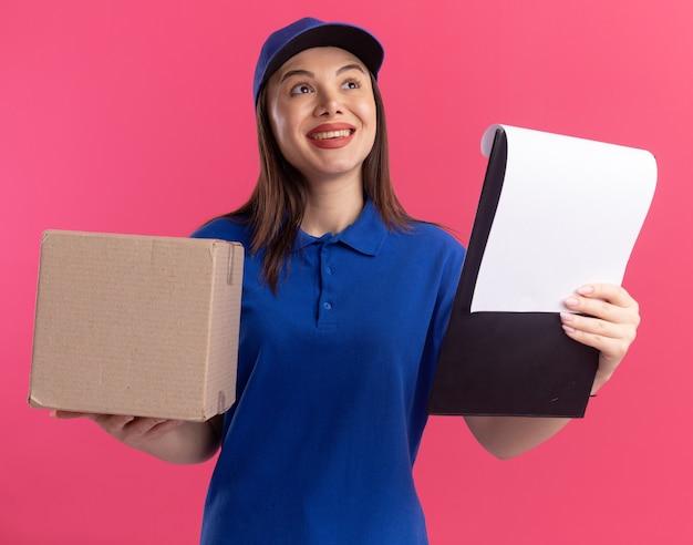 De glimlachende mooie leveringsvrouw in uniform houdt kartonnen doos en klembord die kant op roze bekijken