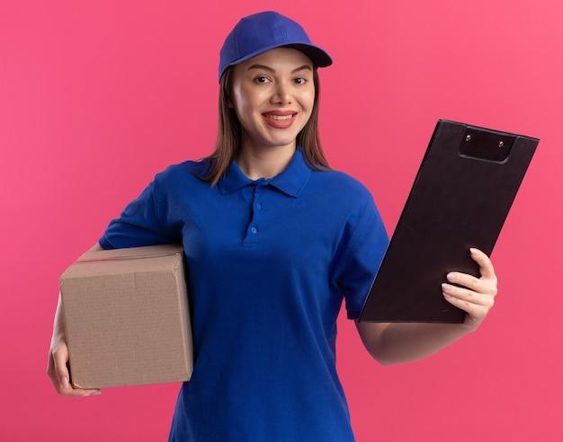 De glimlachende mooie leveringsvrouw in uniform houdt kartonnen doos en klembord geïsoleerd op roze muur met exemplaarruimte