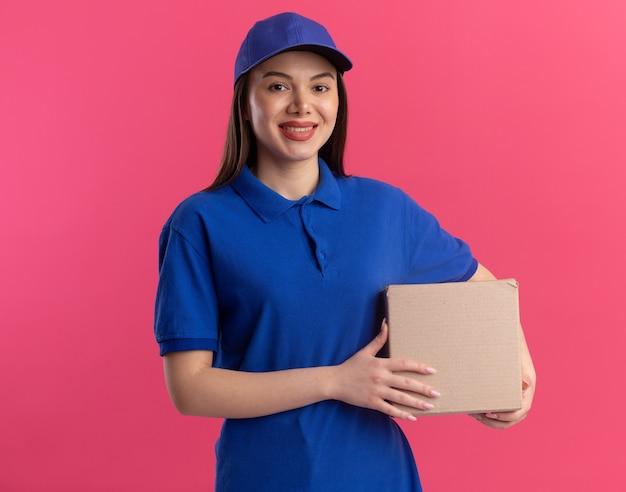 De glimlachende mooie leveringsvrouw in uniform houdt kartonnen doos geïsoleerd op roze muur met exemplaarruimte