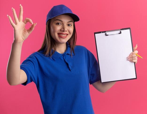 De glimlachende mooie leveringsvrouw in uniform houdt klembord en gebaren ok handteken dat op roze muur met exemplaarruimte wordt geïsoleerd