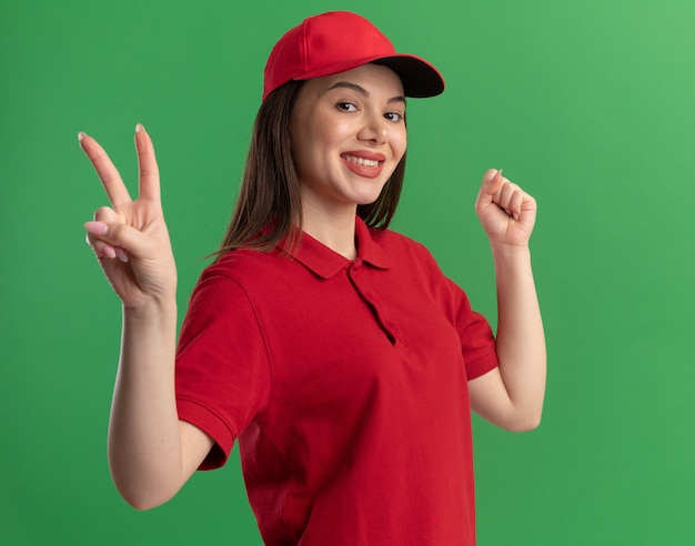 De glimlachende mooie leveringsvrouw in uniform houdt vuist en gebaren overwinning handteken op groen