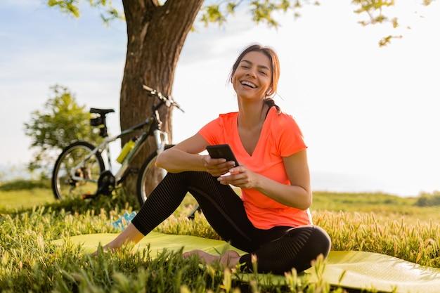 De glimlachende mooie telefoon van de vrouwenholding die sporten in ochtend in park doet
