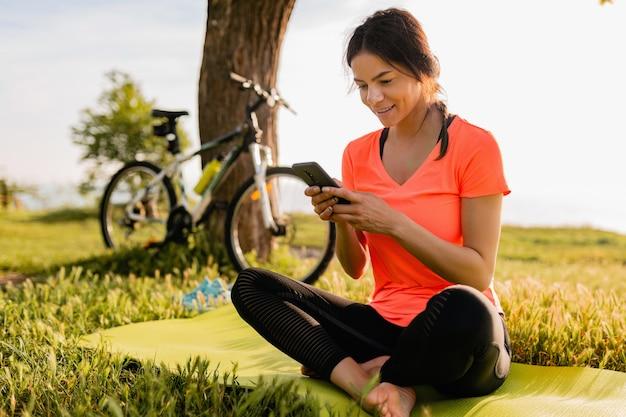 De glimlachende mooie telefoon van de vrouwenholding die sporten in ochtend in parknatuur doet