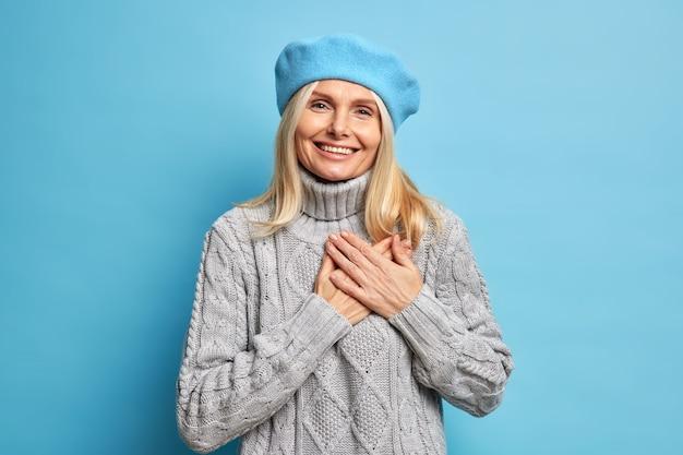 De glimlachende mooie vrouw houdt de handen tot het hart gedrukt drukt zijn dankbaarheid uit, draagt een blauwe baret en een gebreide grijze trui is dankbaar en waardeert uw hulp.