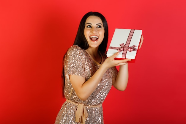 De glimlachende mooie vrouw probeert te raden wat er in de geschenkdoos zit.