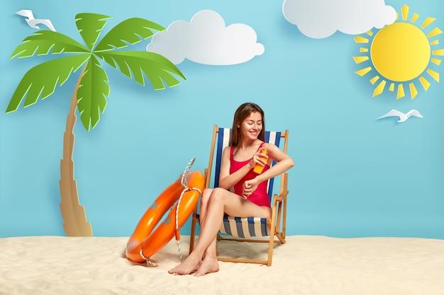 De glimlachende mooie vrouw stelt bij strandstoel