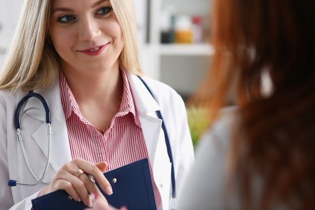 De glimlachende mooie vrouwelijke geneeskunde arts legt uit