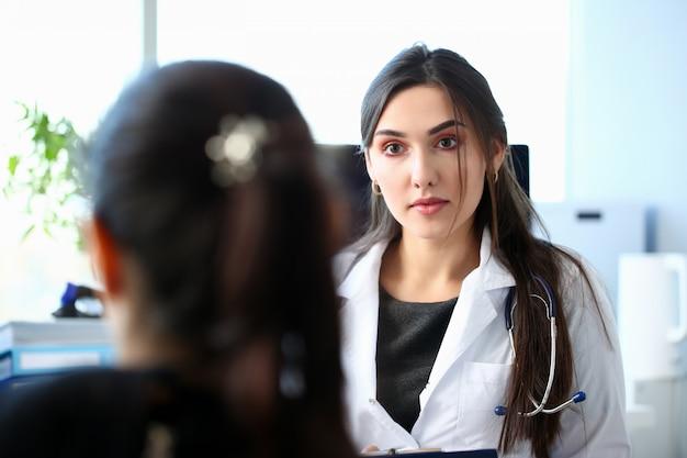 De glimlachende mooie vrouwelijke geneeskunde arts verklaart diagnose