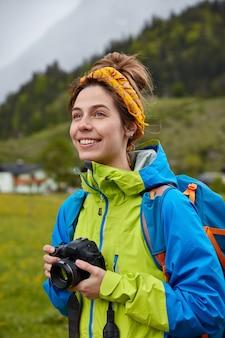 De glimlachende onbezorgde europese vrouw houdt professionele camera, kijkt positief in afstand