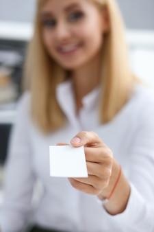 De glimlachende onderneemsterholding dient wit overhemd in en geeft leeg visitekaartje
