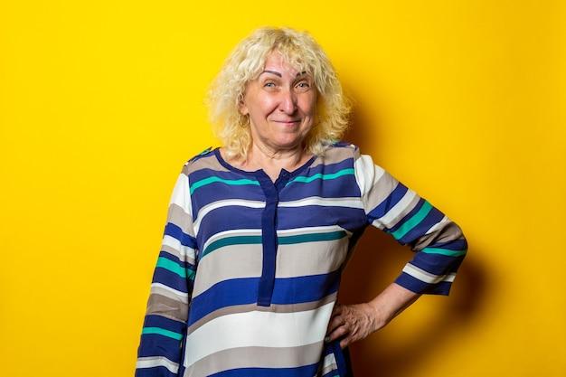 De glimlachende oude vrouw in een gestreepte jurk houdt haar hand in de taille op een gele ondergrond