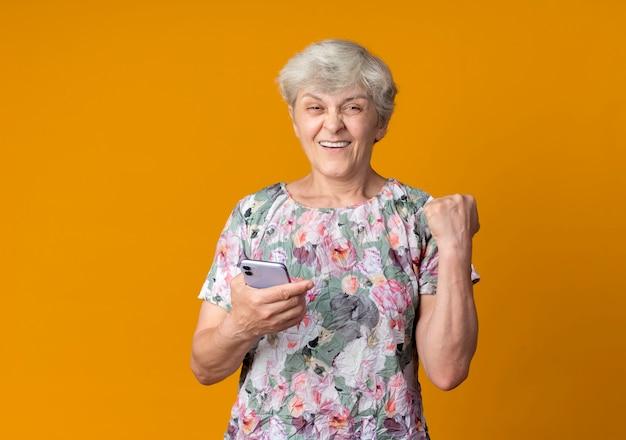 De glimlachende oudere vrouw houdt de telefoon van de vuistholding die op oranje muur wordt geïsoleerd