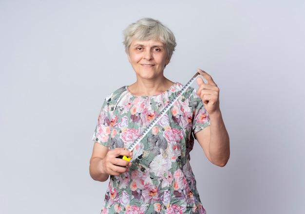 De glimlachende oudere vrouw houdt meetlint geïsoleerd op een witte muur