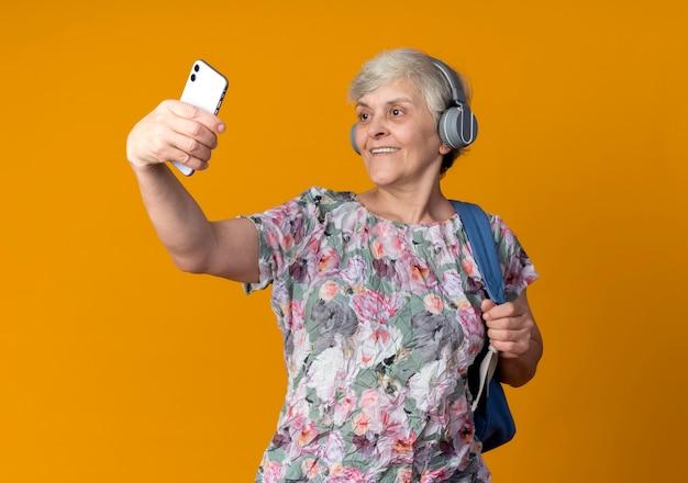 De glimlachende oudere vrouw op hoofdtelefoons die rugzak draagt houdt en kijkt naar telefoon die selfie neemt die op oranje muur wordt geïsoleerd