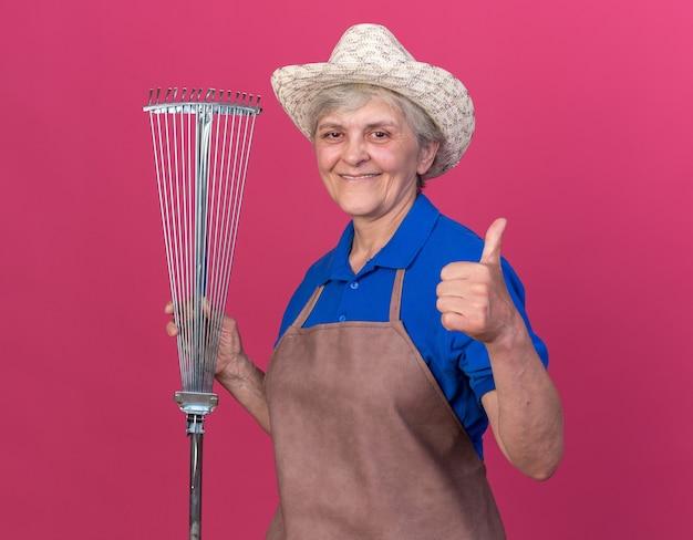 De glimlachende oudere vrouwelijke tuinman die tuinierende hoed draagt houdt bladhark en duimen omhoog op roze