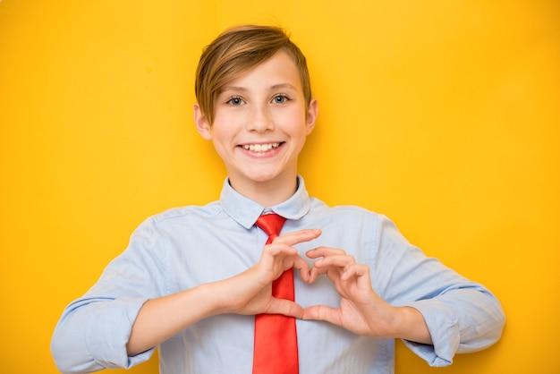 De glimlachende positieve tienerjongen toont hart. valentijnsdag, liefde en creatief concept