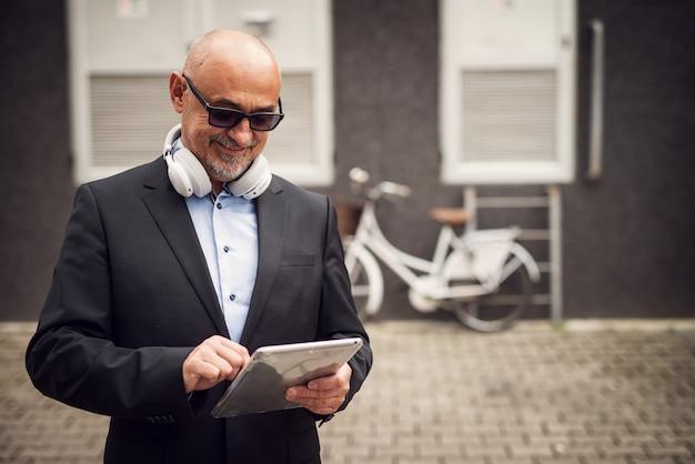 De glimlachende rijpe zakenman gebruikt buiten tablet met een hoofdtelefoon rond zijn hals