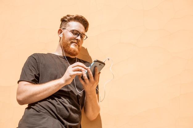 De glimlachende roodharige jonge mens met een baard gebruikt een mobiele telefoon.