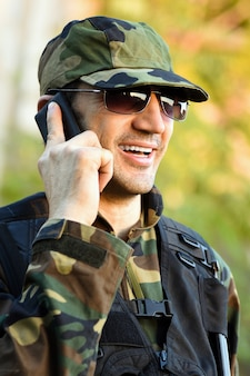 De glimlachende soldaat in uniform praat aan de telefoon.