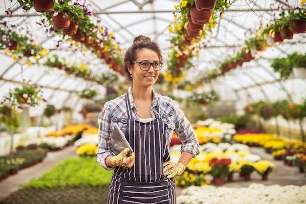 De glimlachende succesvolle vrouw die van de bloemistondernemer zich met een tablet in het serrehoogtepunt bevinden van bloemen en potten.