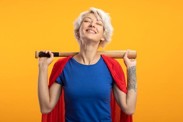De glimlachende supervrouw met rode cape houdt honkbalknuppel achter hals die op oranje muur wordt geïsoleerd