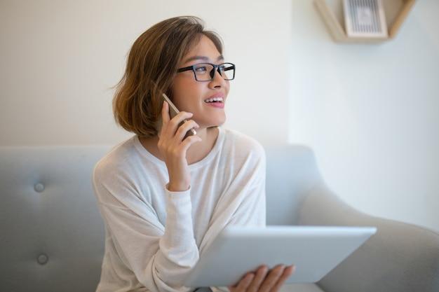 De glimlachende tablet van de vrouwenholding en het spreken op telefoon op bank