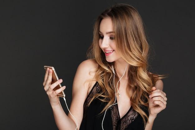 De glimlachende telefoon van de vrouwenholding en het luisteren muziek.