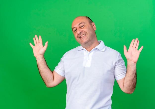 De glimlachende toevallige volwassen mens spreidt handen uit die op groene muur worden geïsoleerd